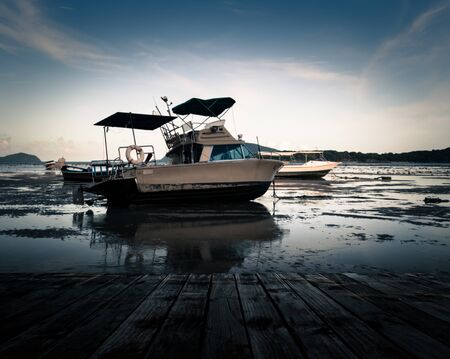 Scenery of the wooden pier with motor boat during low tide photo