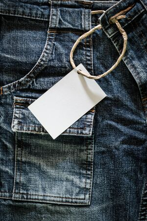 white card: White card on wrinkled jeans background Stock Photo
