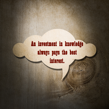 wymowny: Meaningful quote on paper cloud with wooden background, An investment in knowledge always pays the best interest.