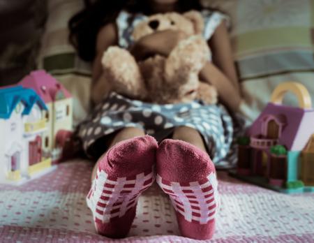 petite fille avec robe: Fermez un peu l'usure du pied chaussettes de fille sur le lit