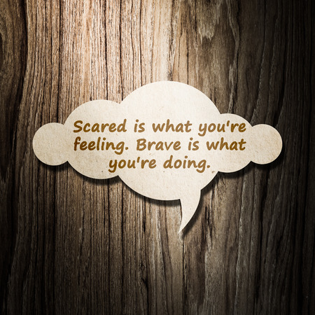 meaningful: Meaningful quote on paper cloud with wooden background, Scared is what youre feeling. Brave is what youre doing. Stock Photo