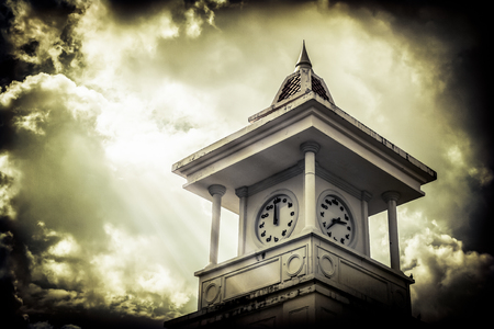 massy: Clock tower with cloudy sky under sunlight on old paper vintage style Stock Photo