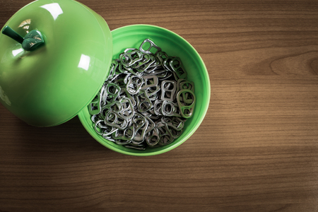 ring pull: Many metal ring pull in green plastic cup on wooden table
