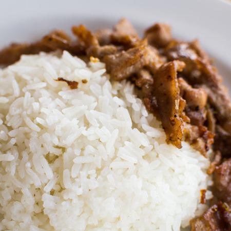 stir up: Close up stir fried pork with pepper and garlic on steam rice