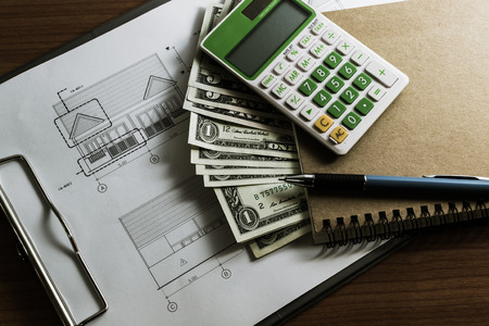 Investment for construction with limit budget, Construction plan, pen, money, notebook and calculator on wooden table