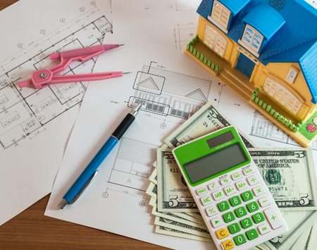 us dollars: Modelhouse, calculator and US Dollars on construction planning with drawing materials Stock Photo
