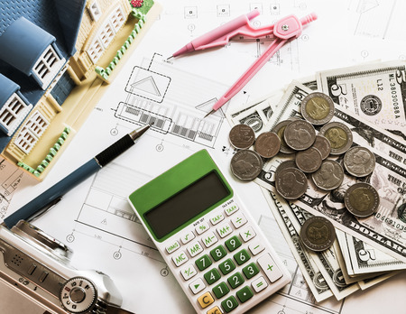 model house: Investment for construction with limit budget, Construction plan, pen, money, model house, compass, camera and calculator on wooden table Stock Photo