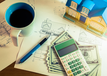 figuring: Investment for construction with limit budget, Construction plan, pen, money, model house, cup of coffee and calculator in cross processed color Stock Photo