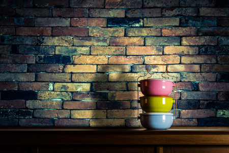 tiffin: Colorful tiffin carrier on wooden cupboard with vintage old brick wall