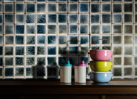 tiffin: Colorful tiffin carrier and plastic bottles on wooden cupboard with vintage tiles wall background against warm light