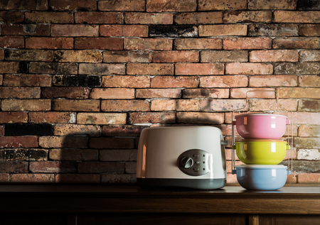tiffin: Colorful tiffin carrier and toaster on wooden cupboard with vintage brick wall background against warm light