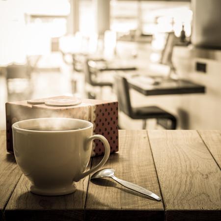 cafe internet: caf� caliente y caja de regalo sobre la mesa de madera en el caf� internet en tono c�lido