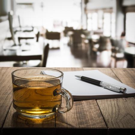 cafe internet: Té caliente con el cuaderno y lápiz sobre tabla de madera en café internet
