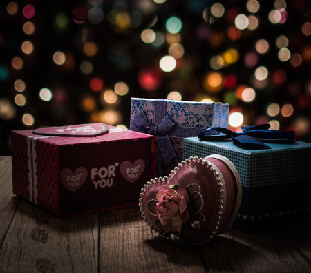shinning light: Gift boxes are on wooden plank under shinning light with colorful bokeh background Stock Photo