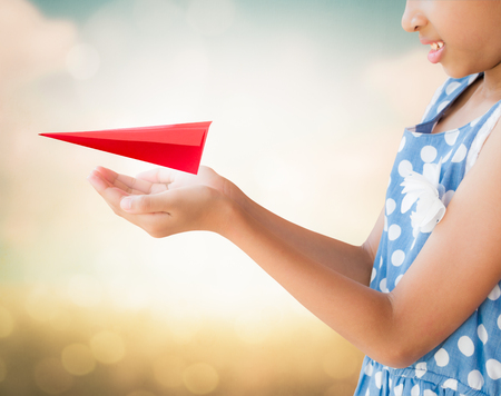 delicated: Little girl taking care and holding red aircraft paper origami with nature background Stock Photo