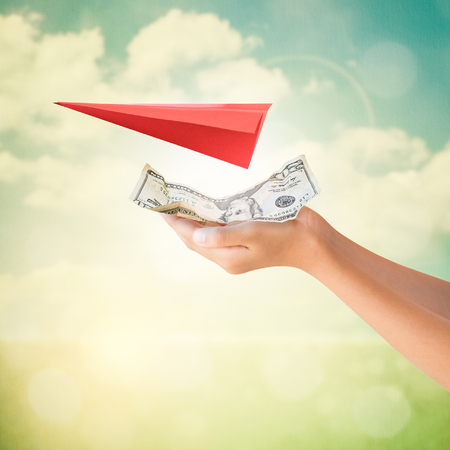 take charge: Hands holding US Dollars note for travel payment with red aircraft origami on summer background