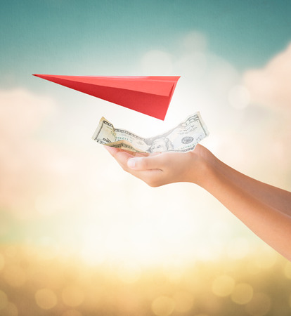 us dollars: Hands holding US Dollars note for travel payment with red aircraft origami on summer background
