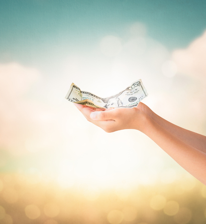 us dollars: Hands holding crumpled US Dollars note with natural summer vintage background, Financial concept