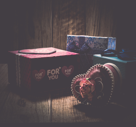 shinning: Gift boxes in wooden box under shinning light in vintage style