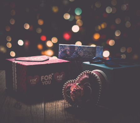 shinning: Gift boxes are on wooden plank under shinning light with colorful bokeh background Stock Photo