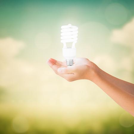 Hands of little girl holding energy saving light bulb on natural vintage paper background