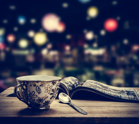 Coffee cup with magazine on wooden table in the vintage coffee shop Stock Photo