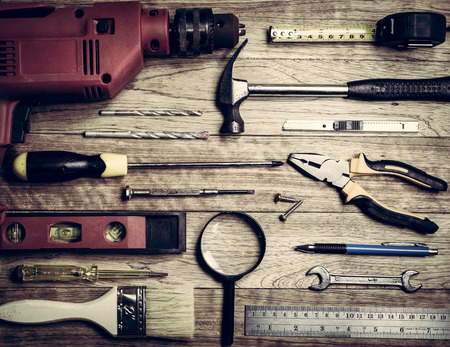 Set of tools over a wooden plank in vintage background Stock Photo