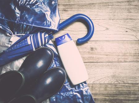 jabon liquido: azul accesorios para la temporada de lluvias, paraguas, botas de caucho, impermeable y jabón líquido en el fondo mesa de madera