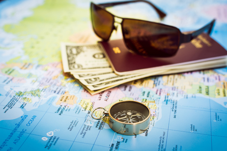 Travel concept, Compass, passport, money and sunglasses on the map