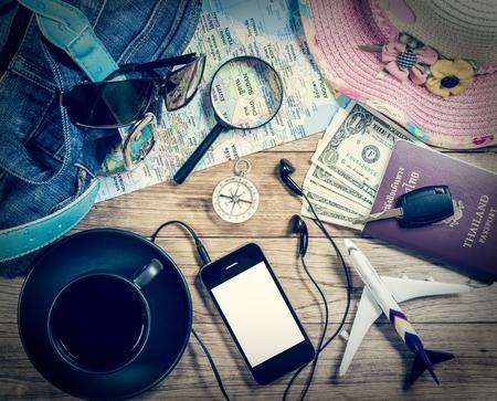 Conjunto de accesorio de viaje con el teléfono inteligente y el café sobre fondo de madera de la vendimia