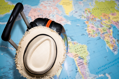 Travel concept, Traveling bag with straw hat on the world map under sunlight