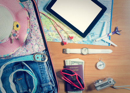 personal accessory: Set of travel accessory in the luggage with tablet and personal items on wooden background