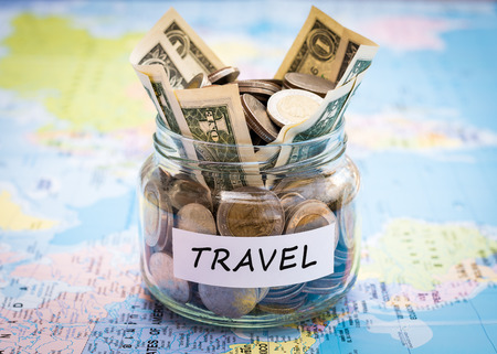 Travel budget concept. Travel money savings in a glass jar on world map