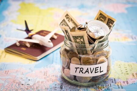 Travel budget concept. Travel money savings in a glass jar with compass, passport and aircraft toy on world map Imagens