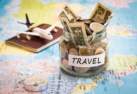 Travel budget concept. Travel money savings in a glass jar with compass, passport and aircraft toy on world map Stockfoto