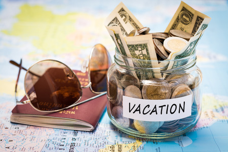 Vacation budget concept. Vacation money savings in a glass jar with passport and sunglasses on world map
