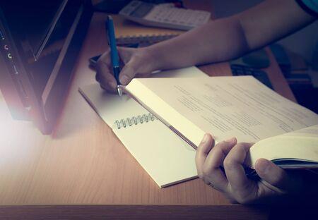 shinning light: Hands of a girl doing homework on the desk with pc under shinning light Stock Photo