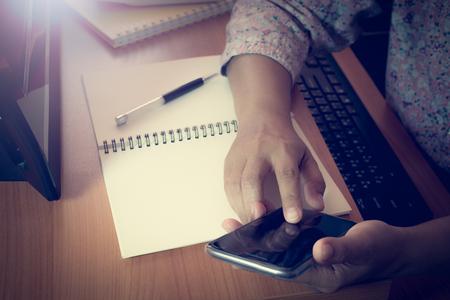 shinning: Hands of business woman touching smart phone screen on office desk under shinning light