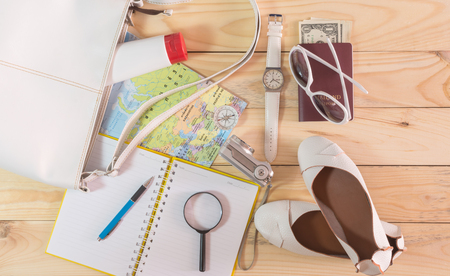 pad and pen: Travel concept with leather handbag, sunglasses, digital camera, world map, passport, money, note pad, pen, magnifying glass, compass, female shoes, body lotion and wristwatch on wooden table
