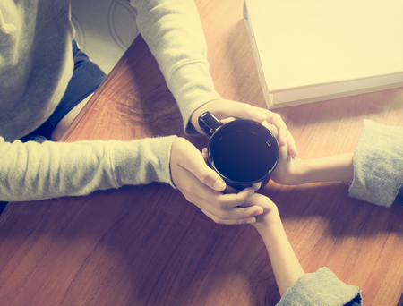 day light: Hands of mother and daughter holding coffee cup on wooden table under shinning light Stock Photo