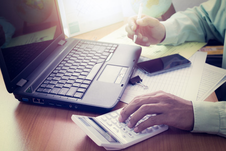 shinning: Hands of a man working with laptop, calculator and holding a pen on office desk in shinning light