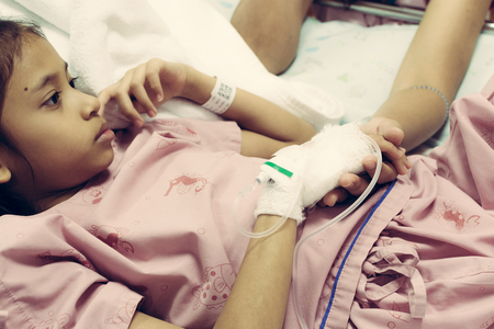 Young daughter sick in hospital and her hand is holding by her mother with care Stock Photo
