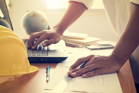 shinning: Hands of architect working on laptop with construction plan under shinning light in office