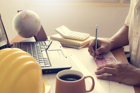 shinning: Hands of architect drawing construction plan with laptop on office desk with shinning light Stock Photo