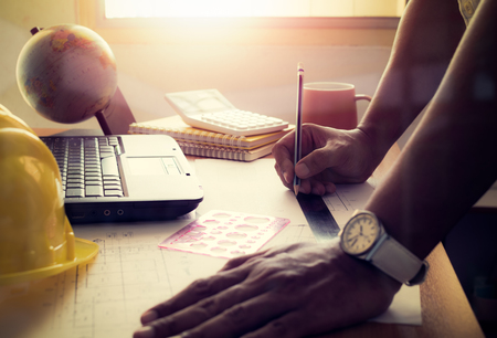shinning: Hands of architect drawing construction plan on office desk with shinning light, film effect. Stock Photo