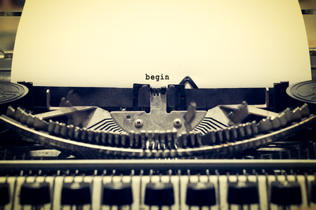 Words begin written with old typewriter on white paper in vintage style