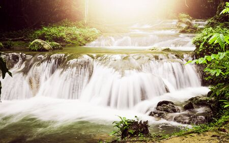 Sa Nang Manora cascade waterfall in tropical rain forest under sunlight, Phang Nga, Thailand