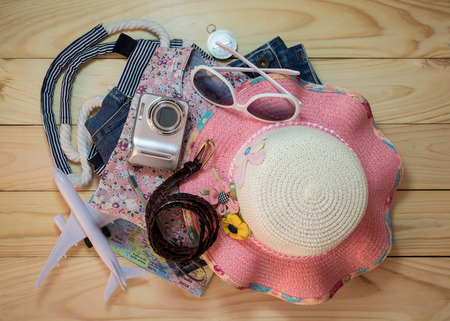Stack of clothes and travel accessory on wooden plank. Travel concept.