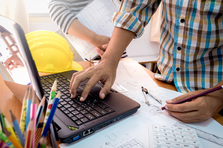 shinning: Architect with partner working with laptop on construction plan in office