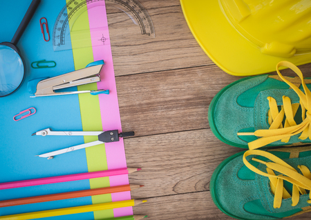 Sneakers, construction helmet, writing material and other on wooden plank, Education concept.